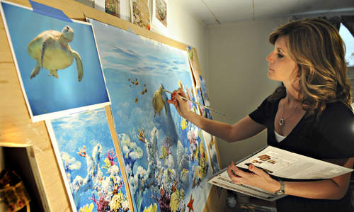 Bonnie Lecat painting a coral reef mural on canvas