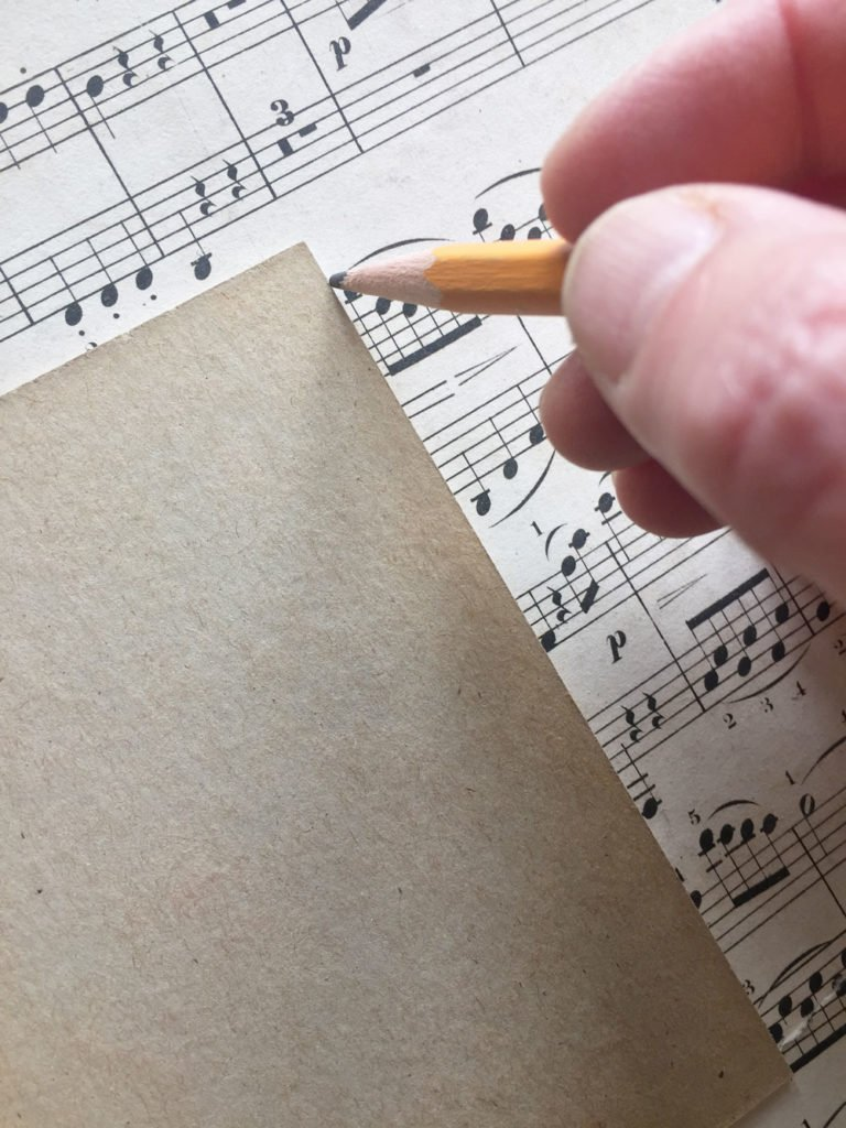 STEP 1) Remove the glass or cardboard insert from your frame and place it over the sheet music print out. Use your pencil to trace around the edge and cut the sheet music to that size.