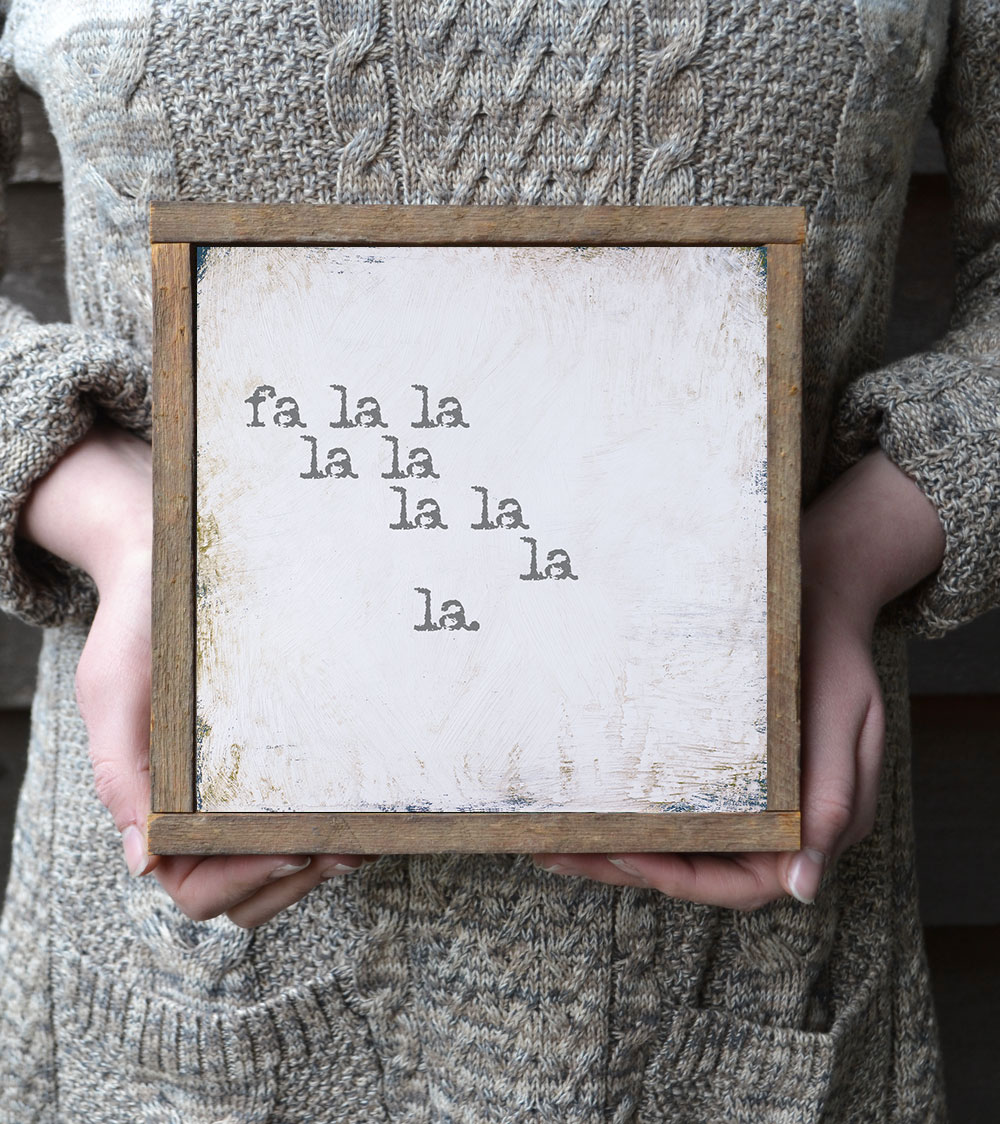 """This cute white and gray Christmas sign features the phrase """"fa la lala la…"""" from the song """"Deck the Halls"""" and is sure to become a family favorite! The simple style and color scheme makes it the perfect addition to update your existing Christmas decor. Also makes a great gift idea! Learn more at https://www.bonnielecatdesigns.com"""